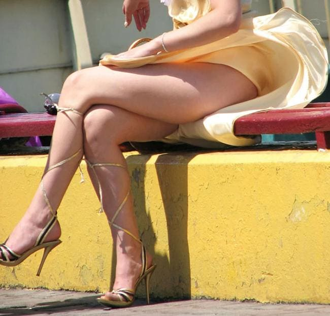 Сидит на парапете ветер поднял юбку обнажив красивые ножки на каблуках в босоножках