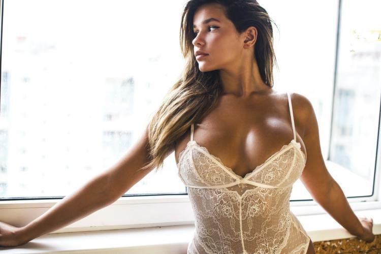 Квитко Анастасия сочные фото стоит у окна опирается на подоконник в белом просвечивающемся боди