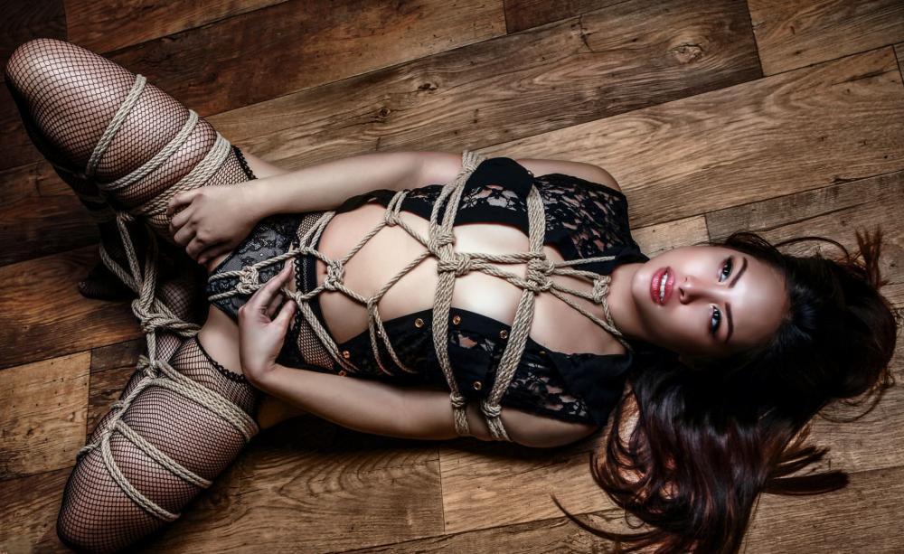 связанная девушка бдсм бондаж шибари в черных в сетку чулках лежит на спине на полу