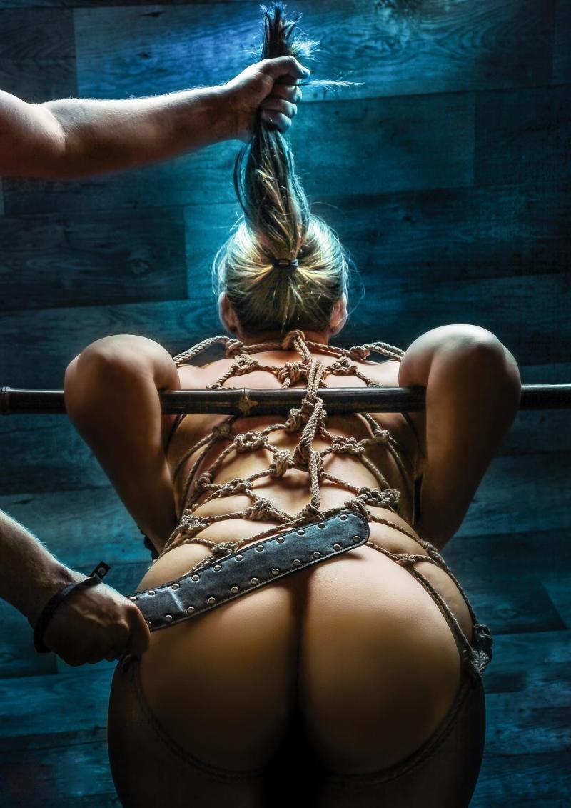 жесткий бдсм девушек блондинка раком руки закинуты за палку, бондаж шибари, держат за хвост и толстой короткой кожаной палкой шлепает по жопе