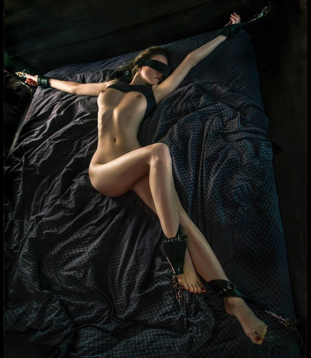 голые девушки бдсм лежит на черном покрывале руки раскинуты в сторону и прикованы, на ногах кандалы, на глазах черная повязка