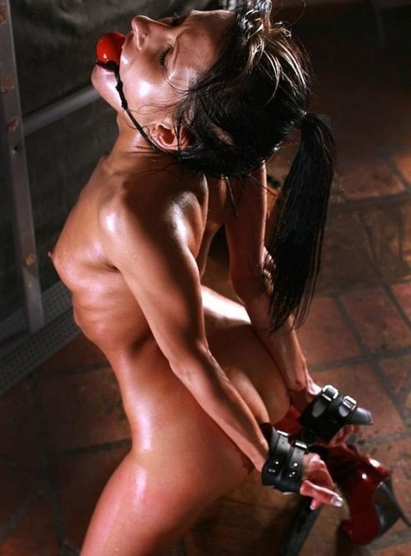 жесткий бдсм девушек голая стоит на коленях с кляпом во рту высоко поднята голова руки связаны широкими кожаными наручниками за спиной