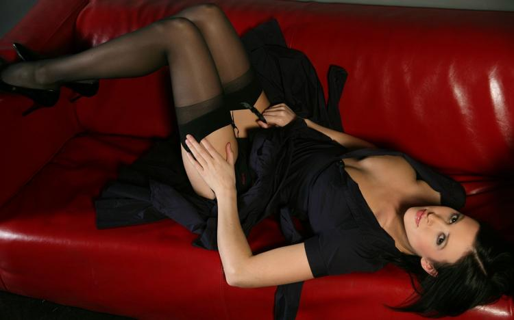сексуальная брюнетка в чулках лежит на диване,задрала платье, вид сверху