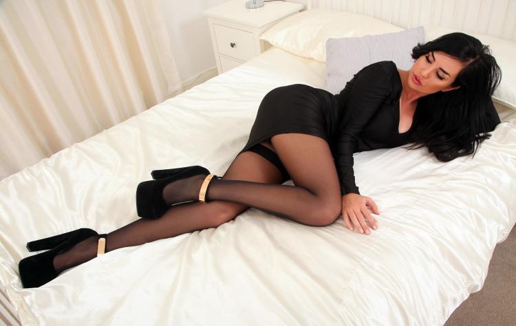сексуальная брюнетка в черных колготках в черном коротком платье лежит на боку на кровати застеленной белым покрывалом