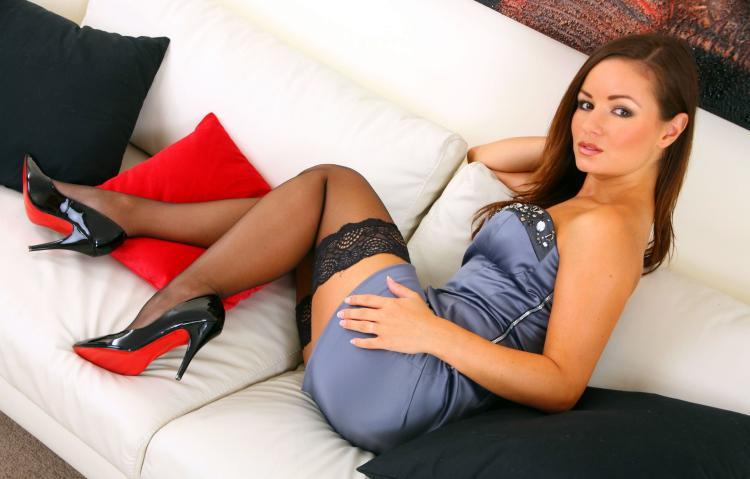 сексуальная девушка брюнетка в коротком стального цвета платье, серных чулках туфлях на высоком каблуке сидит на диване