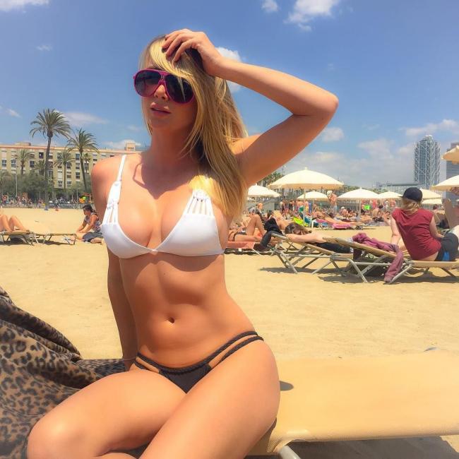 Девушки на пляже в купальниках сидит на шезлонге в очках подняв левую руку на голову