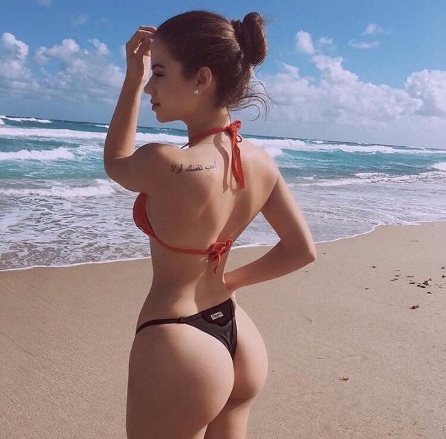 Девушка на берегу моря стоит спиной, показывая свою шикарную жопу в бикини, на правом плече тату