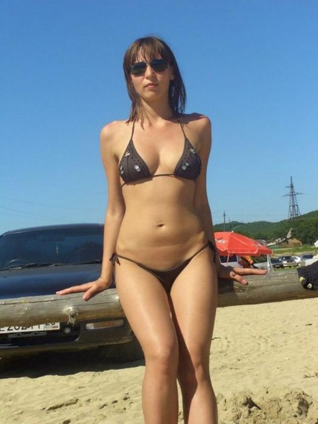Девушка на пляже в очень маленьком бикини.