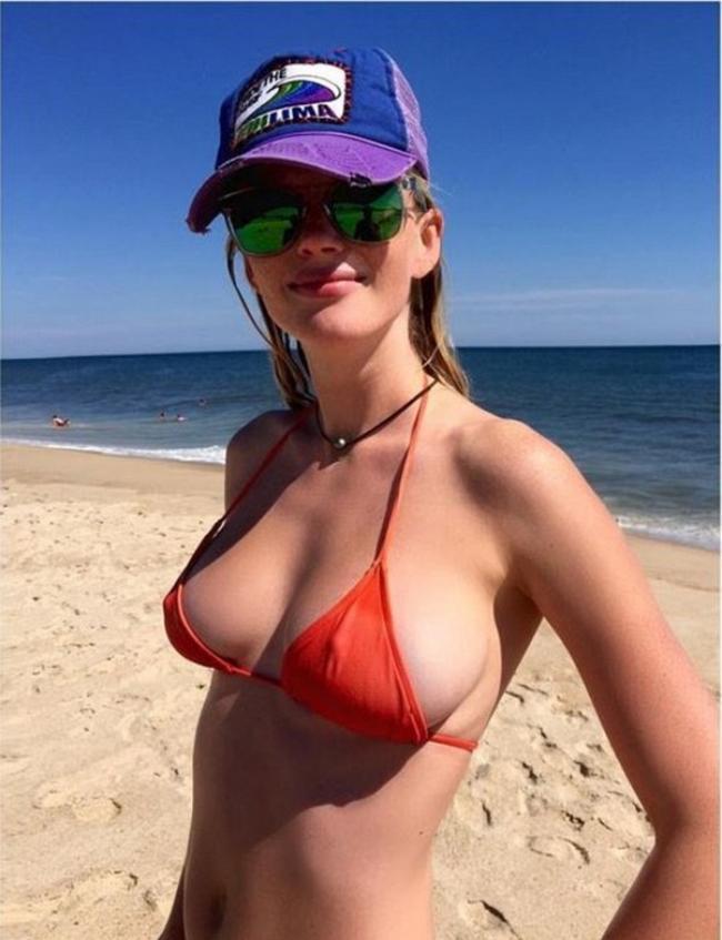 Девушка в мини купальнике на берегу моря с красивой грудью соски стоят
