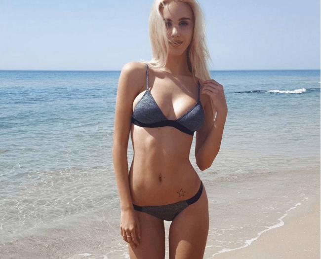 Блондинка в бикинис красивой фигурой у кромки моря.