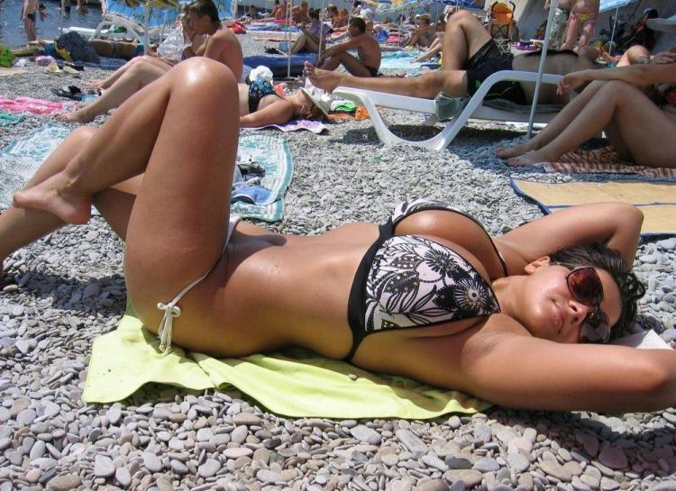 Девушка в купальнике на гальке загорает согнув ноги в коленях, показывая подмышки. Грудь большая