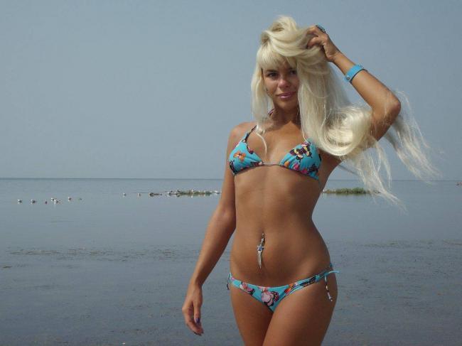 Девушки на пляже красивые блондинка с длинным волосом стоит по колено в море в голубом купальнике бикини, в пупке пирсинг, на руке голубой браслет