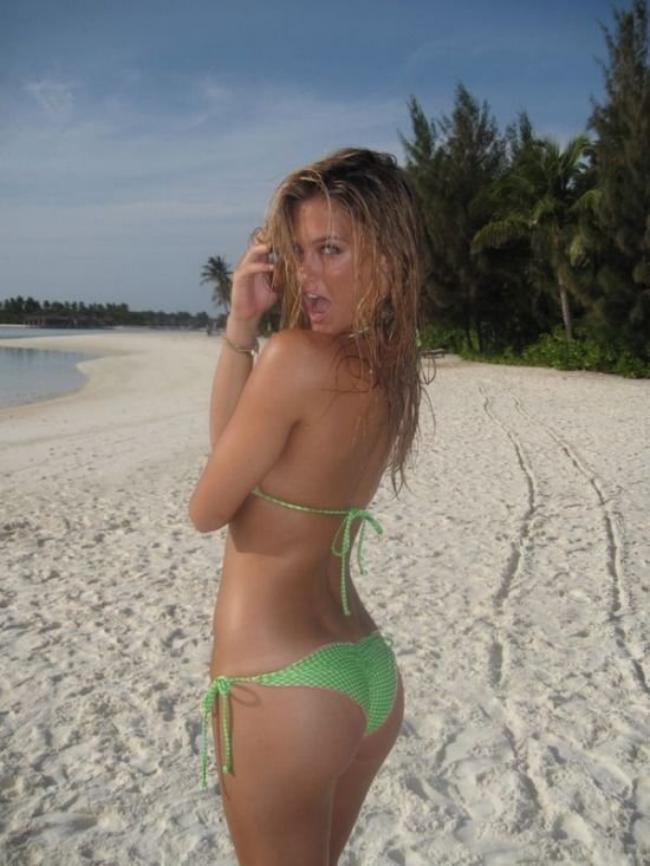Красивые девушки в купальниках на пляже стоит на пляже вполоборота
