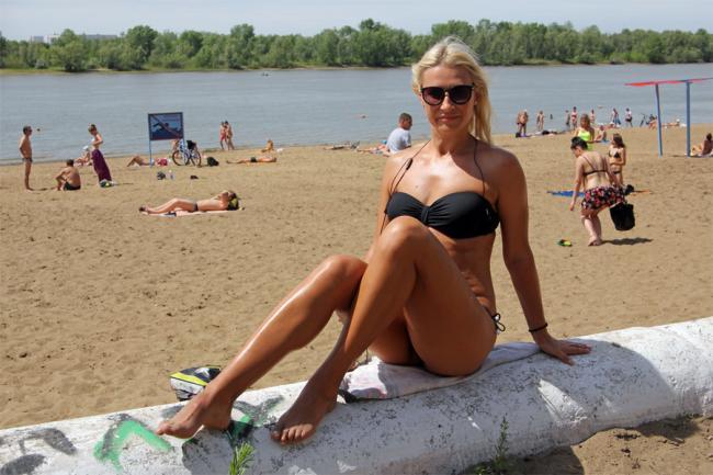 Девушки на пляже красивые сидит на попе согнув ноги в коленях блондинка в очках с распущенным волосом