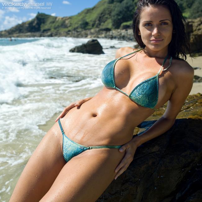 Красивые девушки в купальниках на пляже в бикини брюнетка оперлась на камне на берегу моря