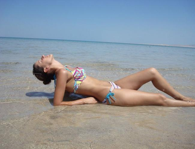 Фото красивых девушек на пляже лежит на спине на берегу моря голову задрала кайфует