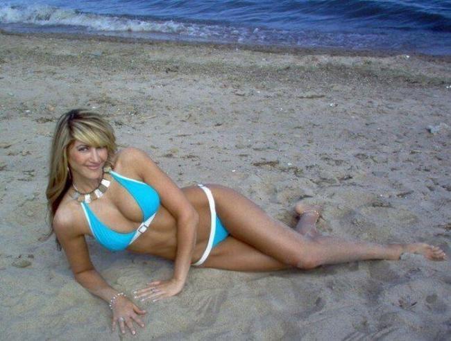 Девушки на пляже красивые ы голубом купальнике блондинка лежит на песке на берегу моря