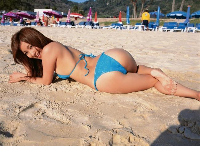 Девушки на пляже красивые лежит на животе в песке в голубом купальнике