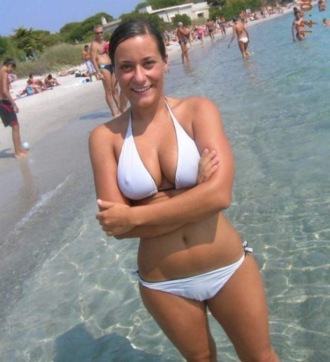 Девушка купальник грудь в белом бикини стоит улыбается по колено в воде