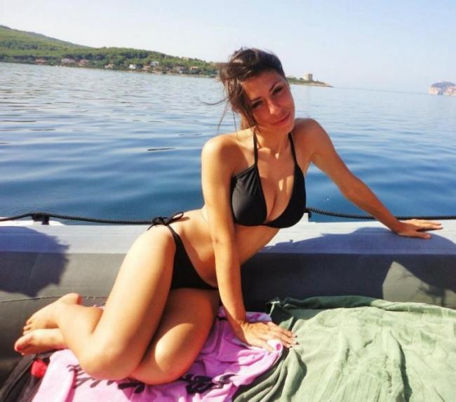 девушка в черном бикини купальнике полусидит на пирсе