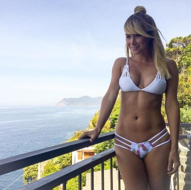 Блондинка в красивом белом купальнике на балконе вид на море