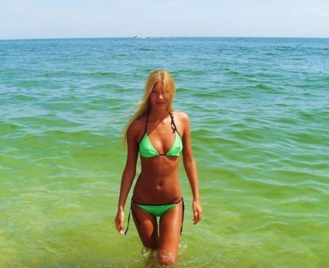 Загорелая блондинка в салатовом бикини на фоне моря.