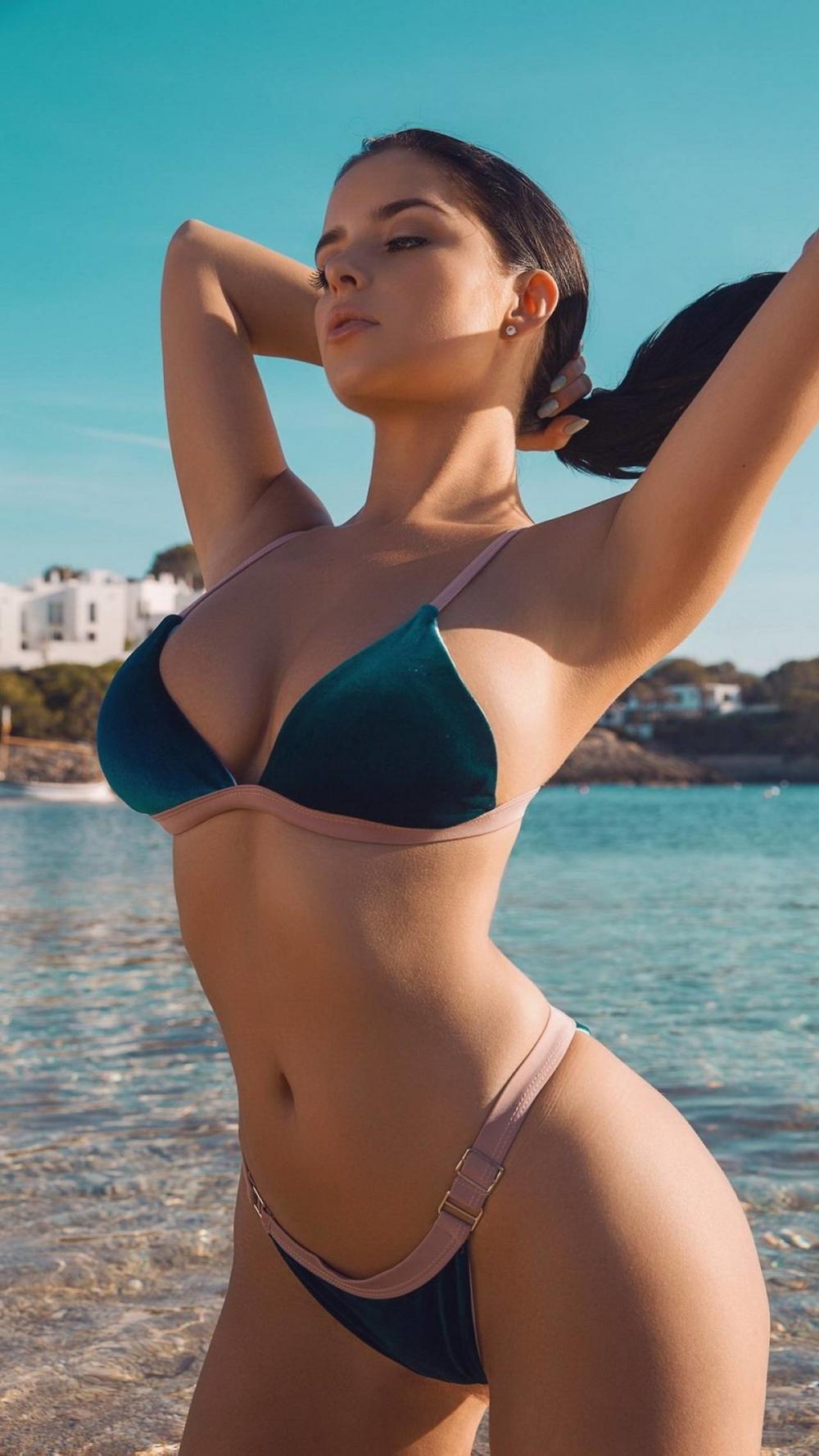 Красивые девушки в купальниках бикини стоит подняв руки и закручивает хвост на голове