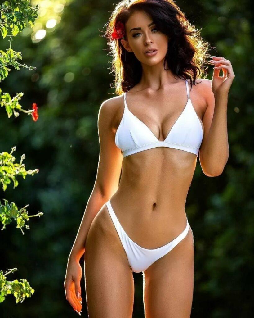 Бикини белые пляж девушки красивая стоит, длинные распушены волосы и красный цветок