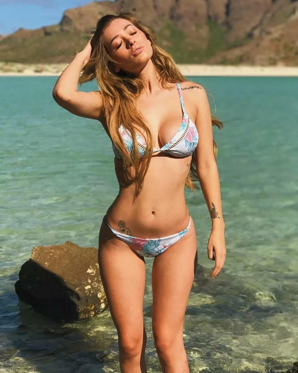 Красивые девушки в купальниках на пляже длинные светлые волосы, глаза прикрыты, правая рука закинута на голову на руке и паху небольшие тату