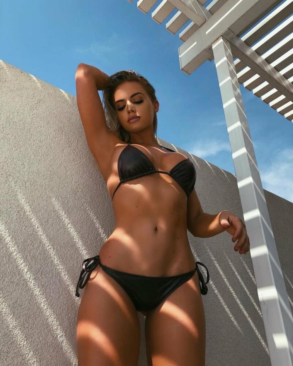 сексуальные девушки в купальниках черном бикини стоит у стены