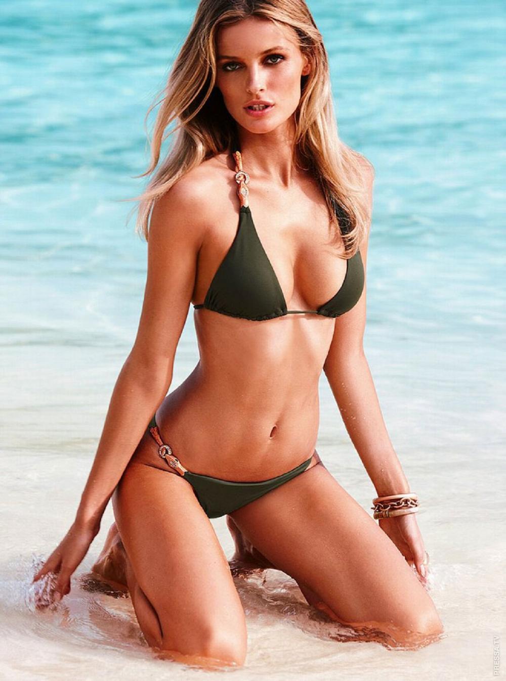 Красивые девушки в купальниках бикини темно зеленого цвета блондинка сидит на коленях на берегу океана