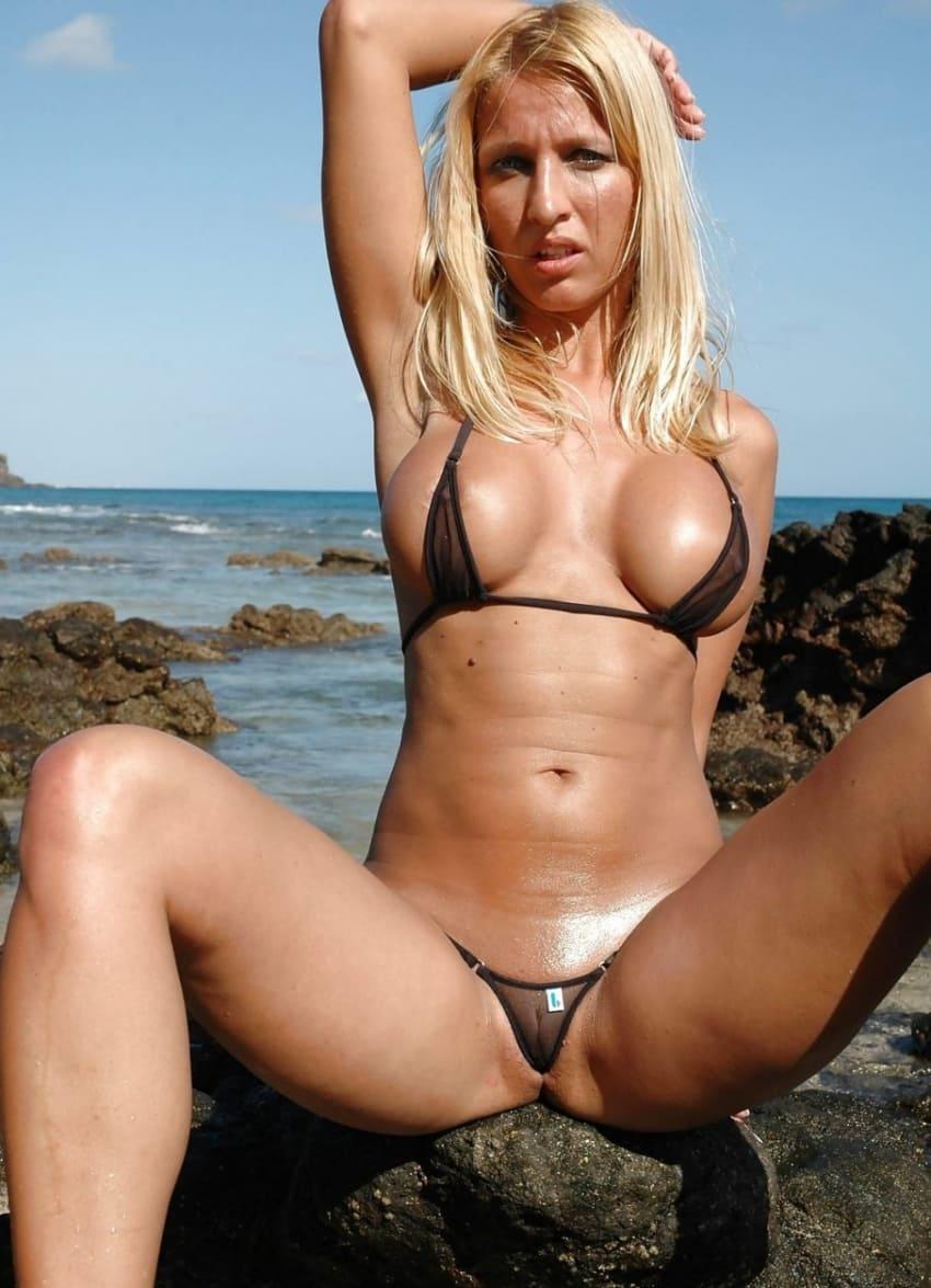 девушки в мини купальниках блондинка загорелая сидит на морских камнях в черном прозрачном микро монокини раздвинула ноги, правую руку закинула за голову оголив бритую подмышку, сиськи большие силиконовые
