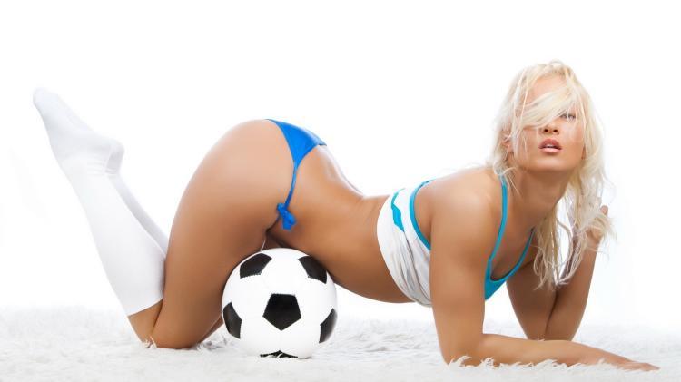 красивые девушки из группы поддержки стоит изогнувшись на коленях в бикини и задранной майке возле мяча