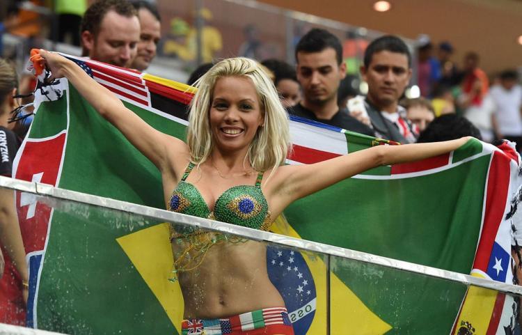девушки группы поддержки фото блондинка стоит держит флаг широко раздвинув руки в бюстике зеленого цвета