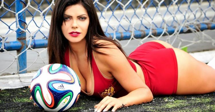 Лежит на животе красивая брюнетка с мячом в воротах в красных шортах и топике