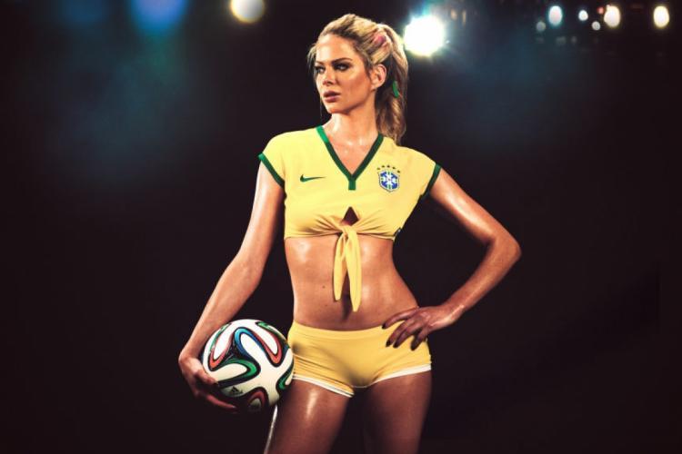 Стоит в желтых шортах и топике с мячом