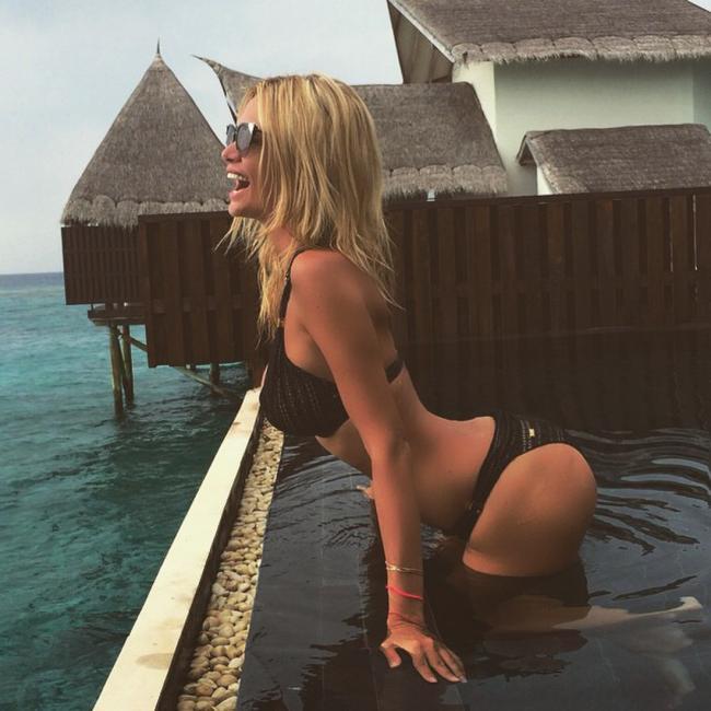 Виктория Лопырева фото на Мальдивах стоит в черном купальнике немного прогнулась вперед, в солнечных очках смеется