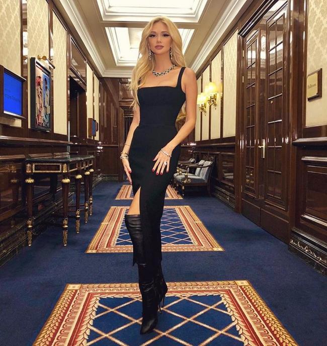 Виктория Лопырева фото стоит в черном обтягивающем длинном платье с большим разрезом и сапогах ботфортах немного выставила правую ногу вперед