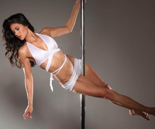 стриптизерша танцует красивая брюнетка с длинным волосом на шесте в белом нижнем белье