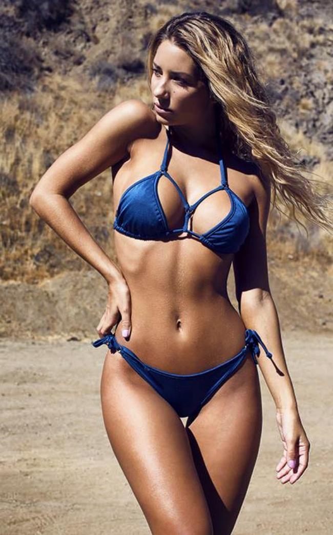 Сиерра Скай в купальнике синего цвета идет по берегу