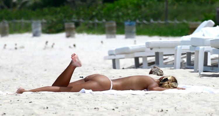 Сиерра Скай лежит на полотенце загорает в белых бикини без лифчика, подняв вверх одну ножку