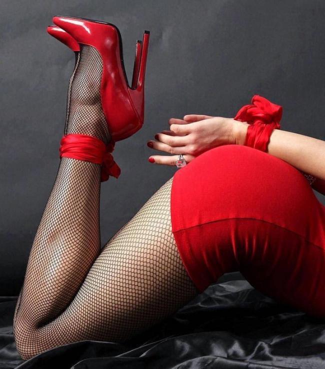 связанные ноги в черных в сеточку чулках и красном платье, руки за спиной связана красной лентой