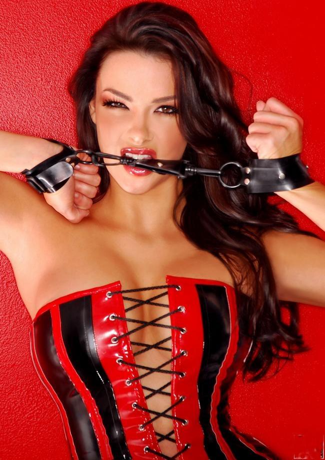 красивая женщина в бдсм наряде из кожи красно-черного цвета со шнуровкой по середине в кожаных наручниках делает вид, что пытается перекусить цепь