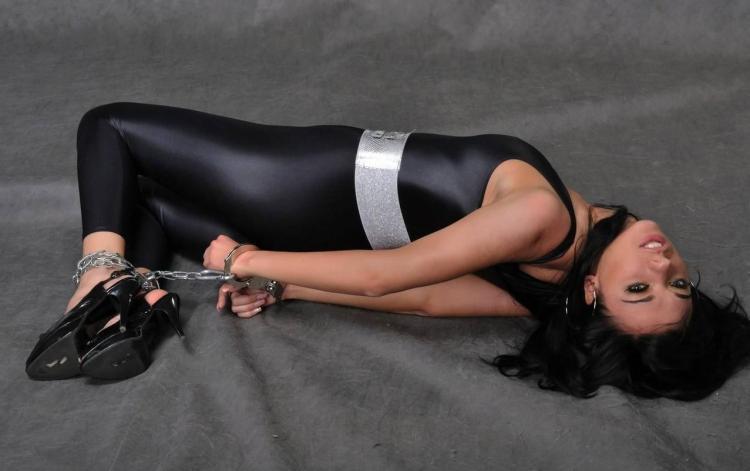 девушка в эластичном костюме черного цвета с серым поясом и черных туфлях на высоком каблуке лежит на полу, у неё скованы за спиной цепью вместе руки притянуты к ногам
