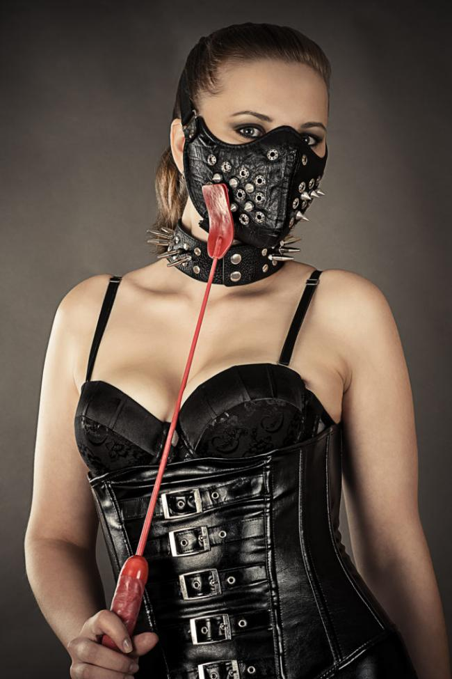 девушка в бдсм костюме из кожи черного цвета с красным хлыстом и проклепанной заклепками и шипами маской на лице и ошейником