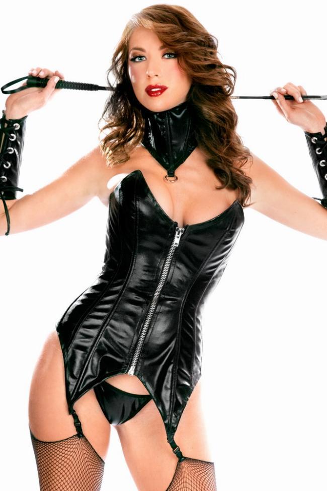 Красивая женщина в кожаном костюме из кожи который застегивается на молнию расположенную по середине, на руках кожаные браслеты со шнуровкой до локтя, на шее широкий ошейник, на ногах черные чулки в сеточку на поясе, в руках за головой держит хлыст, волосы волнистые распущены