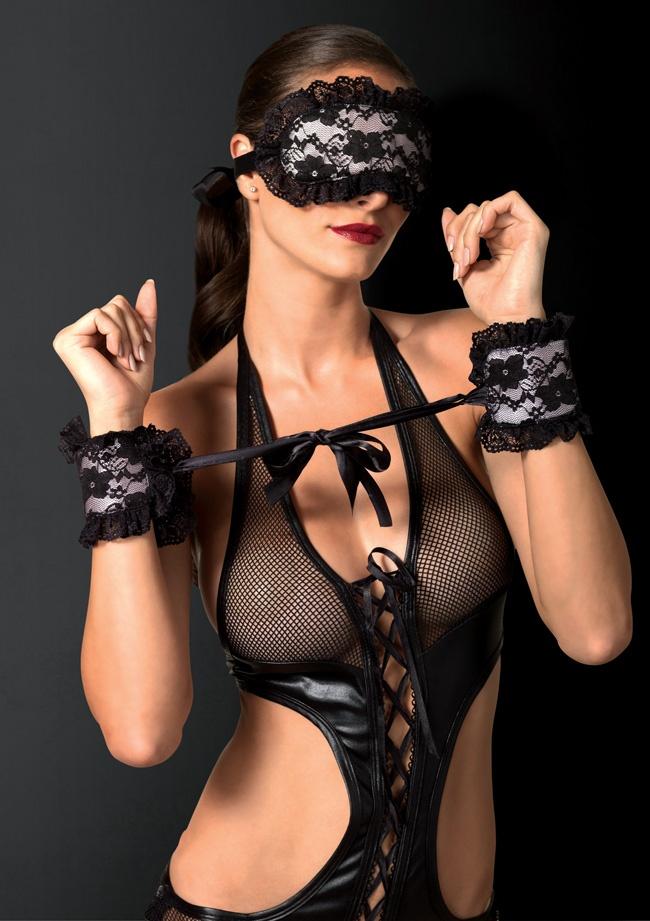Девушка бдсм в костюме из кожзама и капрона в сетку черного цвета на руках надеты наручники из ажурного капрона, на глазах шоры