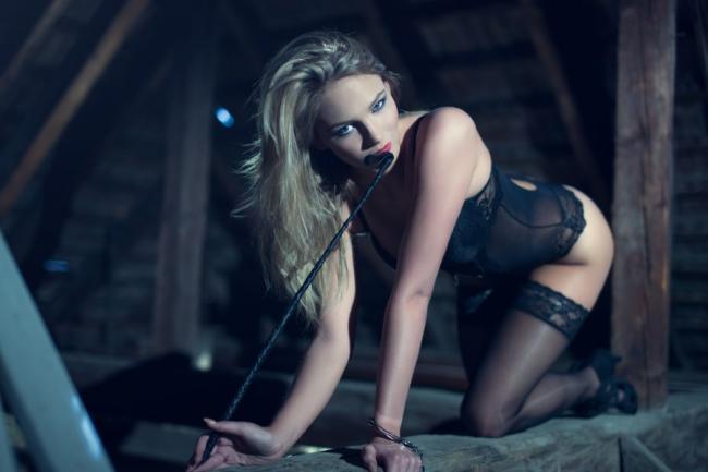 девушка бдсм в черном нижнем белье с хлыстом