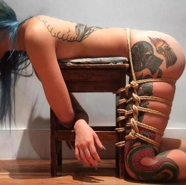 девушка бдсм с татуировкой на ноге и спине стоит на коленях облокатившись грудью на табурет к которому привязана веревкой
