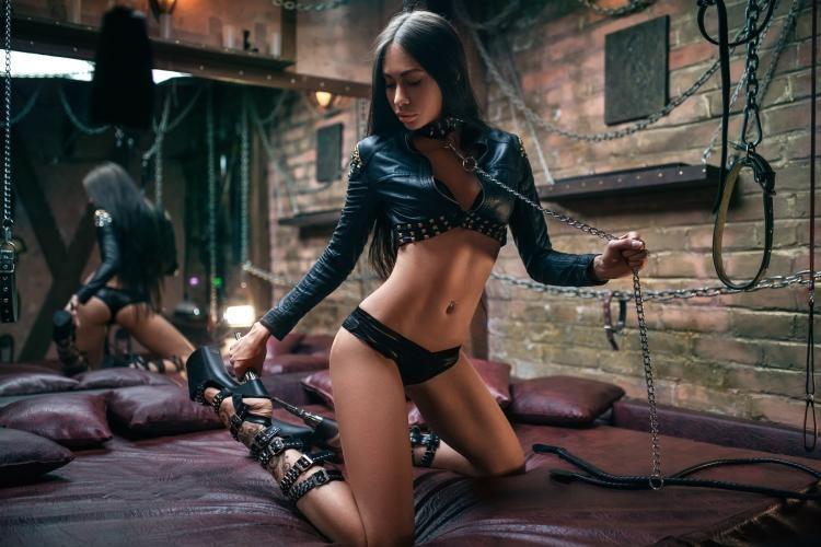 девушка бдсм в туфлях на всокой платформе в трусиках и топе черного цвета стоит на коленях в огромной кровати с зеркалом и держит в руке цепь